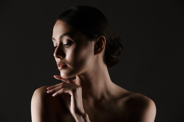 Portrait of sensual beautiful woman looking aside while touching her chin in low lights, isolated over black