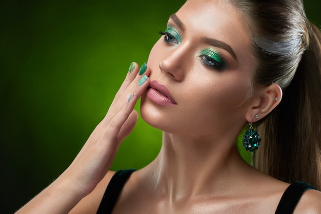 Portrait of sensual beautiful woman with shiny green makeup touching perfect bronze skin of face and plump lips. brunette woman wearing in black top, big rounded earring posing .