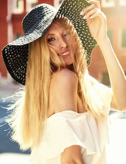 Portrait of sensual blonde woman model dressed in white dress and summer beach hat posing on the street background behind sunset
