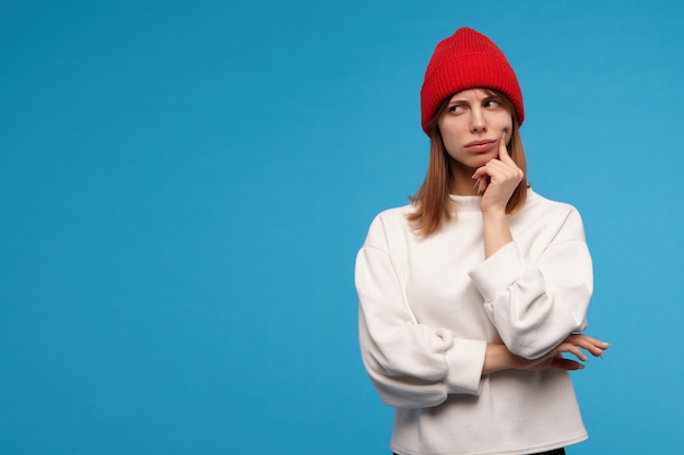Portrait of serious, adult girl with brunette hair. wearing white sweater and red hat. touching her cheek with a finger and think. watching to the left at copy space, isolated over blue wall