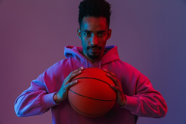 Portrait of serious african american man in colorful hoodie  with basketball isolated over violet wall