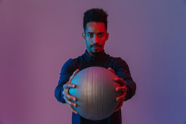 Portrait of serious african american man in sportswear posingwith fitball isolated over violet wall