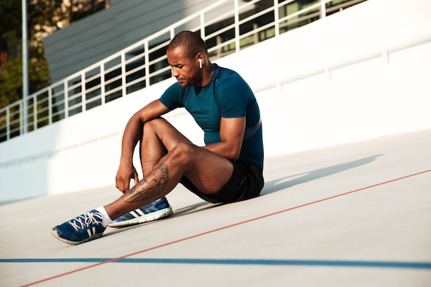 Portrait of a serious african fitness man in earphones resting