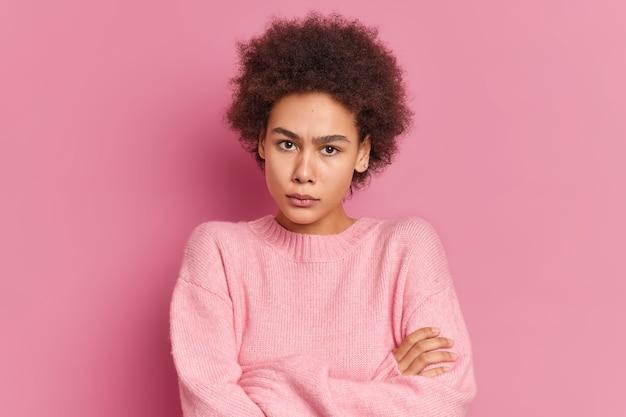 Il ritratto della donna afroamericana arrabbiata seria sta con le braccia incrociate sembra irritato