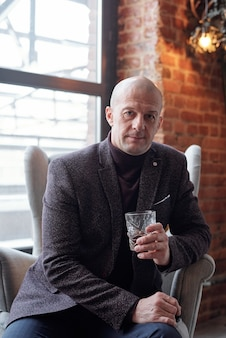 Portrait of serious bald businessman in stylish jacket sitting in armchair in loft room and drinking hard liquor