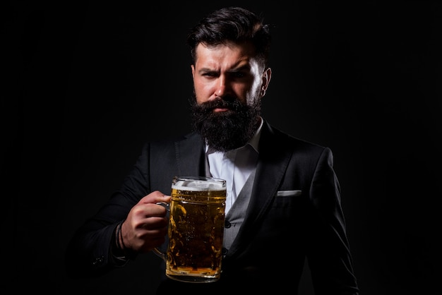 Portrait of serious bearded man drinking beer. happy brewer holding glass with beer.