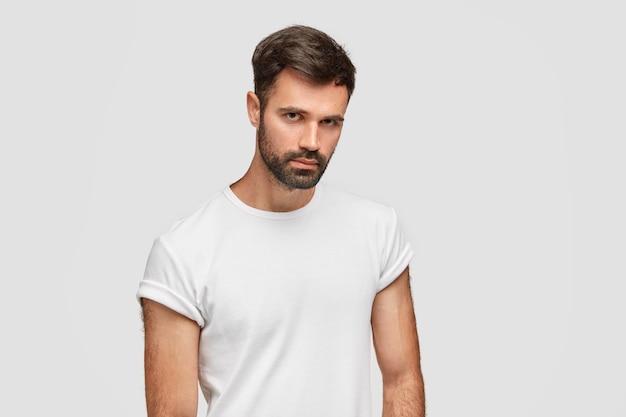 Ritratto di hipster uomo barbuto serio guarda con fiducia