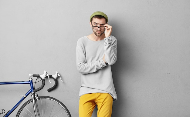 Portrait of serious bearded man looking through glasses, wearing loose sweater and yellow trousers. repairman going to repair bicycle, having clever expression