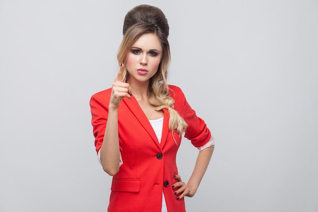 Portrait of serious beautiful business lady with hairstyle and makeup in red fancy blazer, standing with hand on waist and alarm sign looking at camera. studio shot, isolated on grey background.