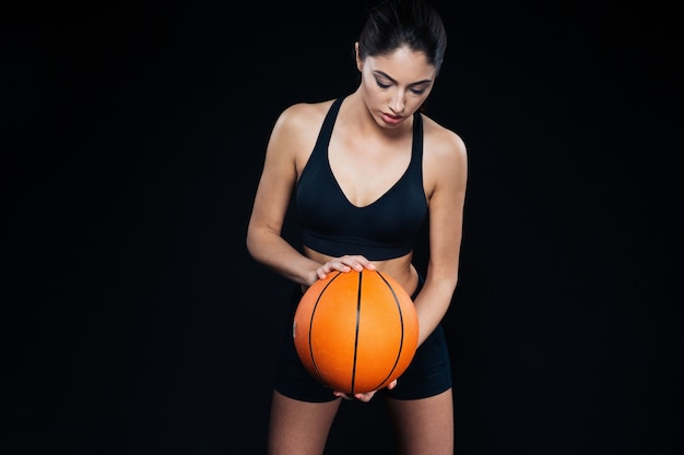 Portrait of serious beautiful young fitness girl with orange basketball ball over black background