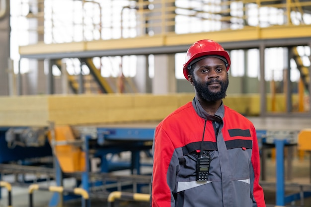 Portrait of serious black laborer with walkie-talkie device on jacket working at constriction plant