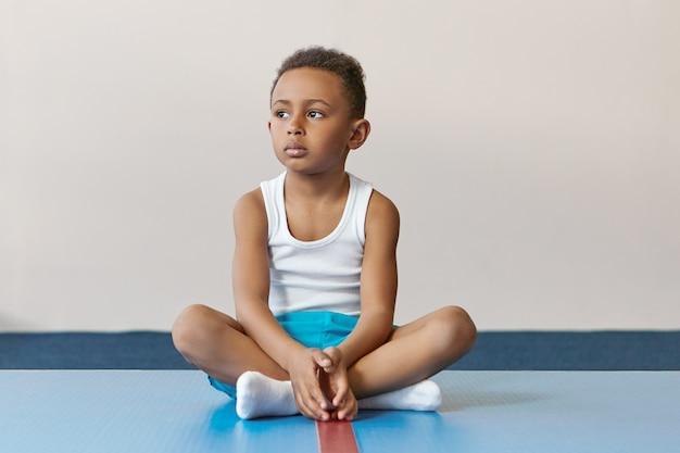 Ritratto di piccolo sportivo nero serio in calzini bianchi, maglietta e pantaloncini blu seduto sulla stuoia da solo