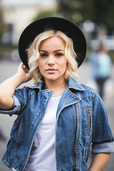 Portrait of serious blonde girl in city centre dressed up in jeans suite and white t-shirt and black hat