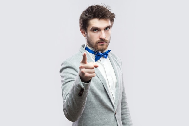 Portrait of serious bossy handsome bearded man in casual grey suit and blue bow tie standing, looking at camera and warming. indoor studio shot, isolated on light grey background.