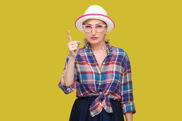 Portrait of serious bossy modern stylish mature woman in casual style with hat and eyeglasses standing with warn sign and looking at camera. indoor studio shot isolated on yellow background.