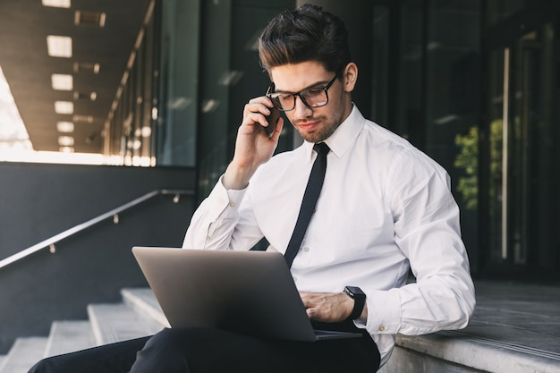Portrait of serious businessman dressed in formal suit sitting outside glass building with laptop, and speaking on cell phone