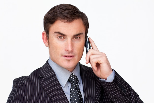 Portrait of a serious businessman on phone against white