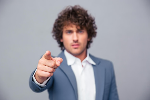 Portrait of a serious businessman pointing finger at front over gray wall. focus on hand