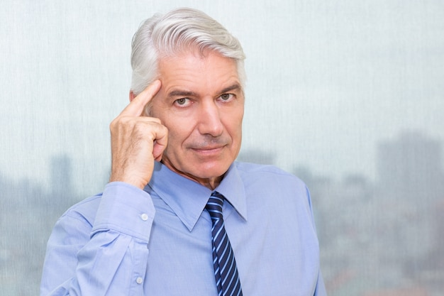 Portrait of serious businessman pointing at head