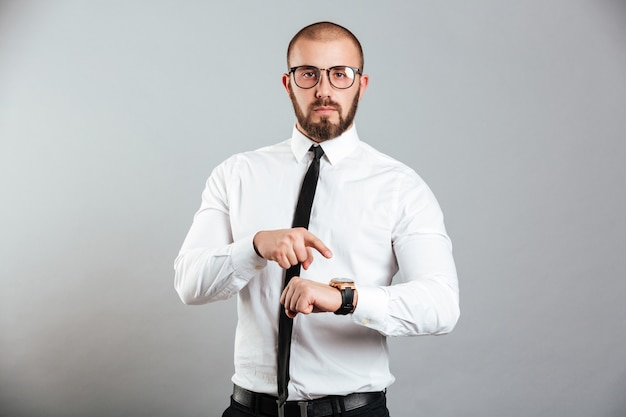 Portrait of a serious businessman pointing