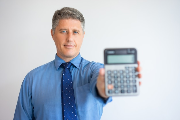 Portrait of serious businessman showing calculator