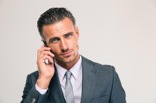 Portrait of a serious businessman talking on the phone isolated. looking at camera