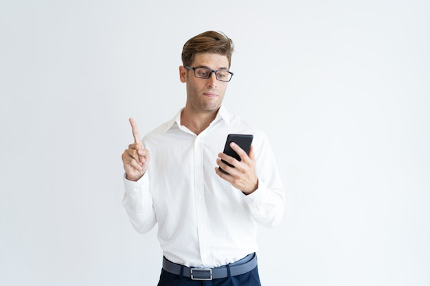 Portrait of serious businessman using phone showing idea gesture