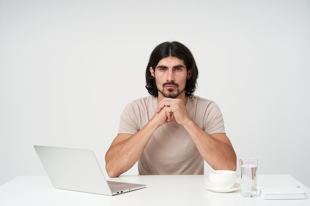 Ritratto di uomo d'affari serio con barba e capelli neri. concetto di ufficio. tiene le braccia unite e appoggia il mento su di esse. seduto sul posto di lavoro e isolato su un muro bianco