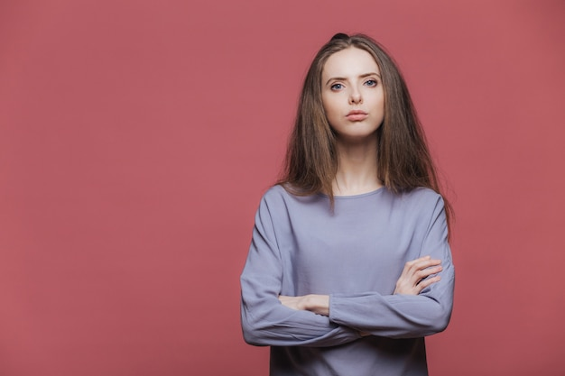 Portrait of serious businesswoman being sure in herself, keeps arms folded, wears casual sweater