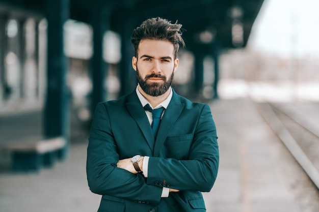Portrait of serious caucasian bearded businessman in formal wear standing at train station with arms crossed.