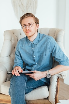 Portrait of serious caucasian man psychologist sitting in armchair at the workplace, holding a folder with papers for notes.