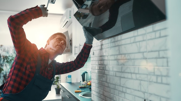 Portrait of serious caucasian repairman in uniform standing in the kitchen. he holds screwdriver and tries to fix the fan. repair service concept. horizontal shot