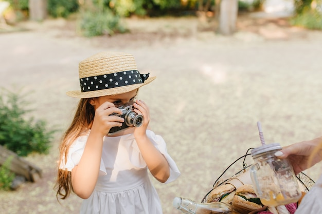 Portrait of serious child with camera wears trendy boater hat decorated with black ribbon. little girl with brown hair taking photo of picnic basket holding her mother.