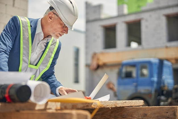 Portrait of a serious civil engineer examining his house plans on a wooden table outdoors