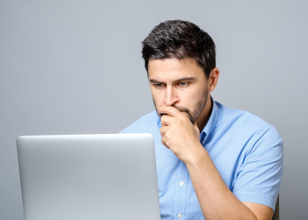 Portrait of serious concentrated man working at laptop