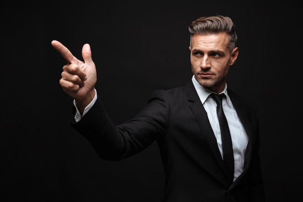 Portrait of serious confident businessman dressed in formal suit pointing finger and looking aside over black wall