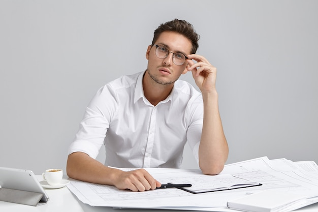 Portrait of serious confident male architect works on blueprint, wears white formal shirt and rounded glasses
