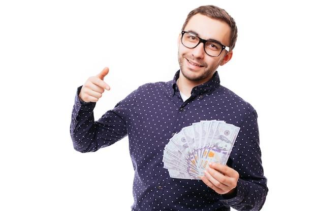 Ritratto di un uomo serio e sicuro di sé che tiene in mano un mucchio di banconote e punta il dito davanti isolato su un muro bianco
