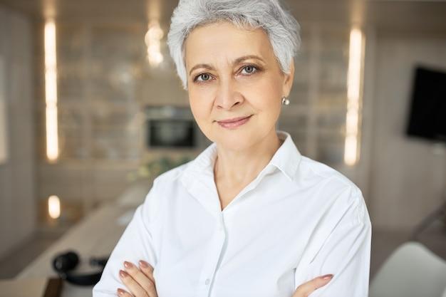 Ritratto di donna di mezza età seria fiduciosa con i capelli corti grigi, occhi verdi, rughe e sorriso affascinante in posa all'interno con le braccia conserte