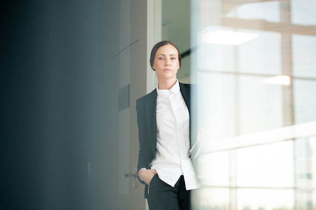 Portrait of serious confident office woman in white blouse and jacket moving over corridor