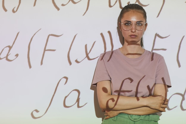 Portrait of serious confident smart girl in eyeglasses standing with crossed arms against projection screen with math formulas