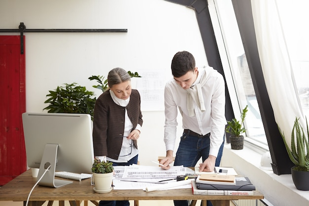 Portrait of serious creative professional designers young man and senior woman working on project, standing at office desk, creating interior designs of residential houses and commercial property