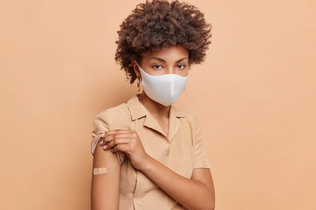 Portrait of serious curly haired woman rolls up sleeve of dress shows vaccination place wears adhesive bandage on arm recieves antivirus vaccine to safe life wears protective face mask poses indoor