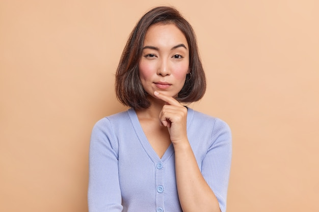 Portrait of serious dark haired asian woman keeps finger on chin looks mysteriously at front considers something dressed in blue jumper isolated over brown wall