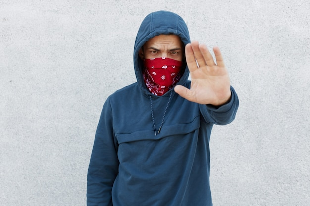 Portrait of serious disappointed protester against black citizens lawlessness,guy showing stop gesture with his palm, stop murder people, activist wearing jumper with hoody and bandana mask.