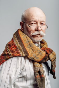Portrait of serious elderly man in glasses on grey