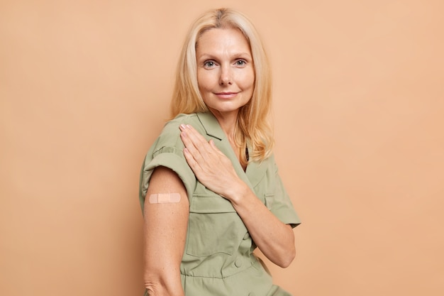 Portrait of serious european woman with minimal makeup blonde hair shows plastered arm gets vaccine as prevention against covid 19 looks directly at front wears dress