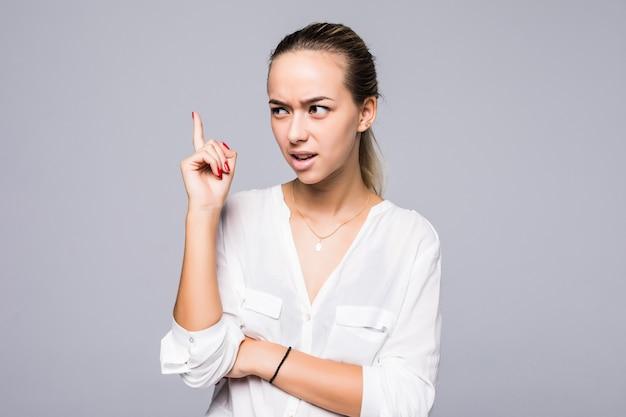 Ritratto serio, accigliato, arrabbiato, scontroso giovane donna che punta il dito verso l'alto, rimproverando qualcuno isolato muro grigio