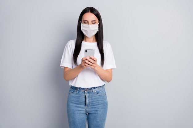 Portrait of serious girl in respiratory mask use smartphone search social media epidemic information wear tshirt denim jeans isolated over gray color background