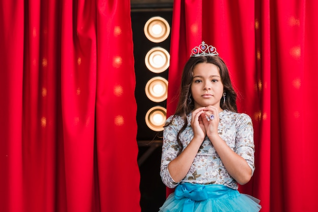 Portrait of serious girl standing in front of red curtain with stage light